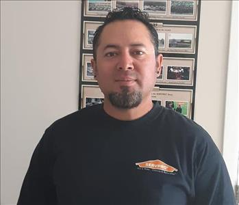 A man wearing a long sleeve black shirt with SERVPRO written on it.