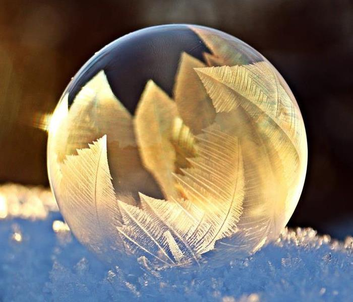 Frozen Bubble filled with ice crystals sitting on top of snow